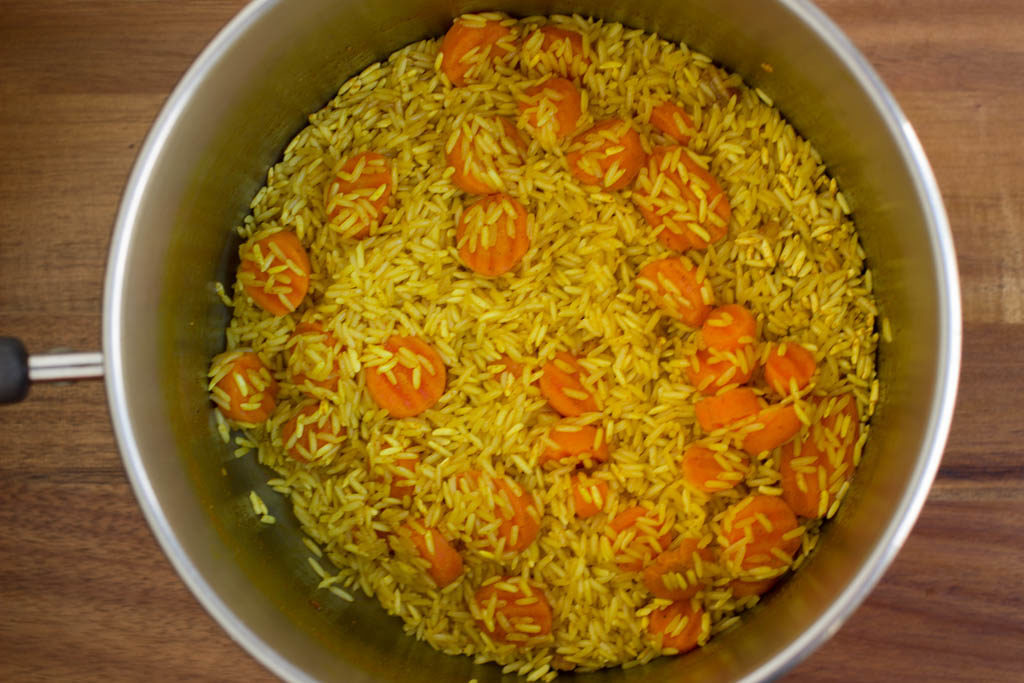 Yellow rice and carrots in a pot.