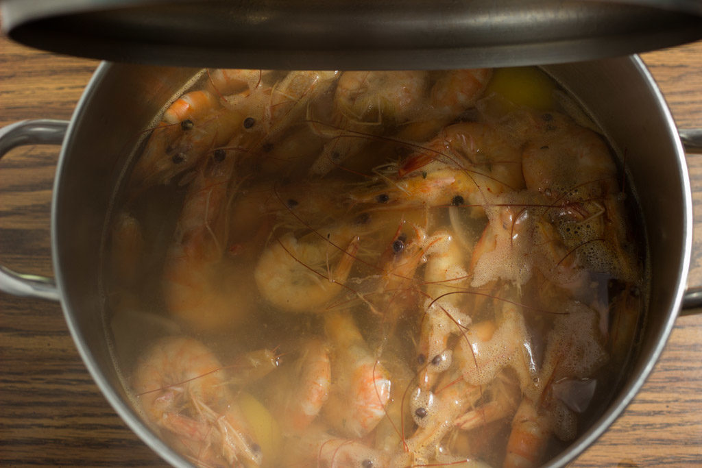 Lid being placed on pot of shrimp.