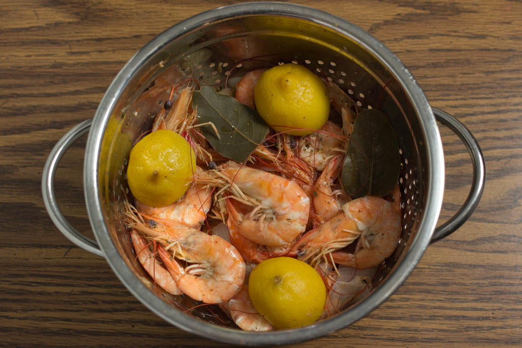 Cooked shrimp draining in a colander.