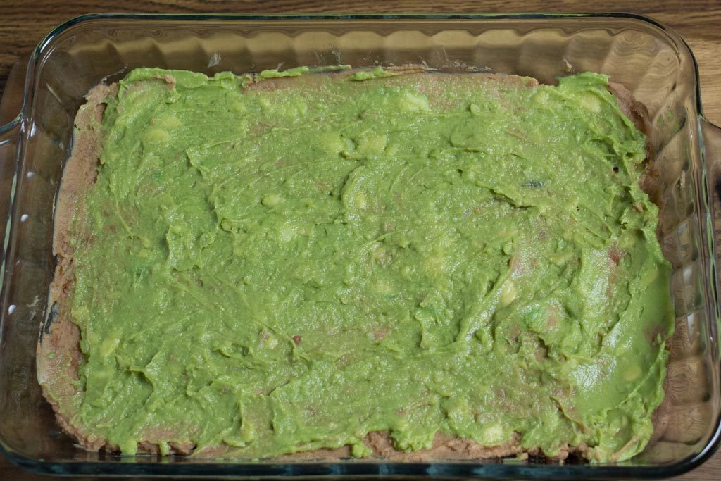 Guacamole is spread on top of the beans.