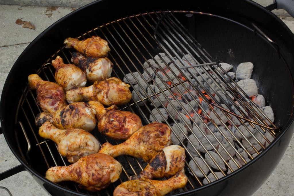 Chicken legs cooking over indirect heat on a Weber grill